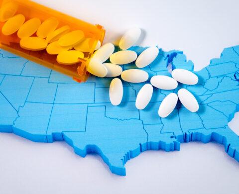 White pharmaceutical pills spilling from prescription bottle over American flag